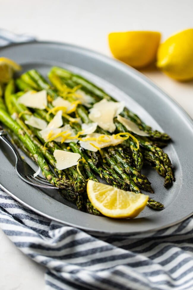 roasted asparagus recipe on platter with lemon and parmesan cheese