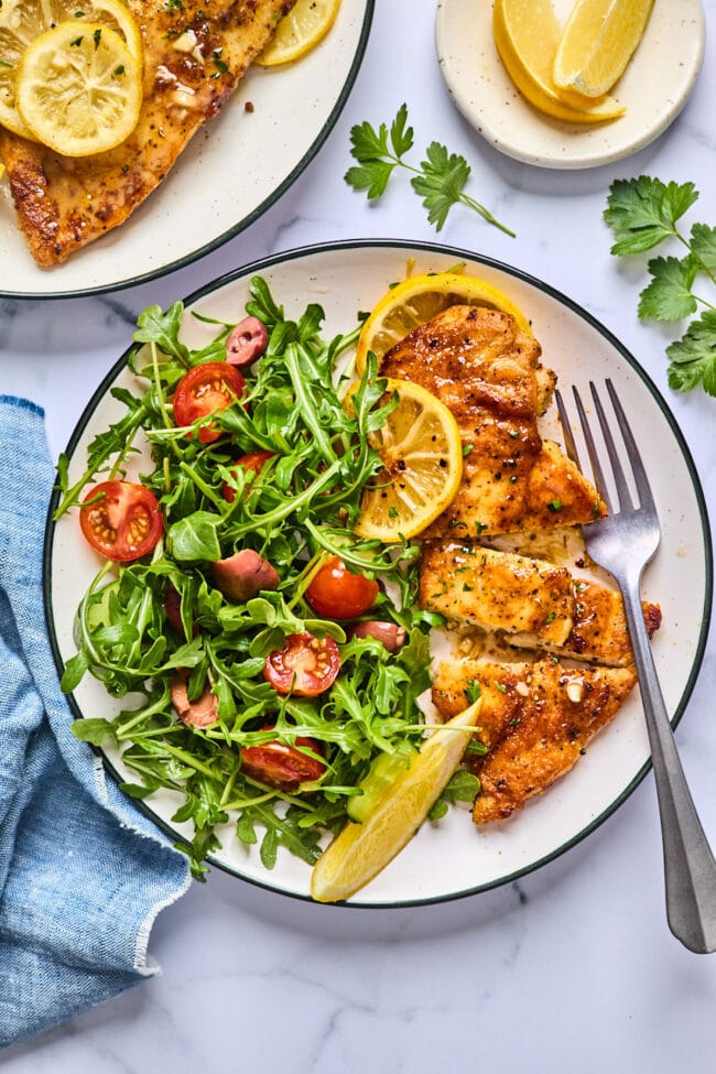 baked lemon butter chicken on plate with salad