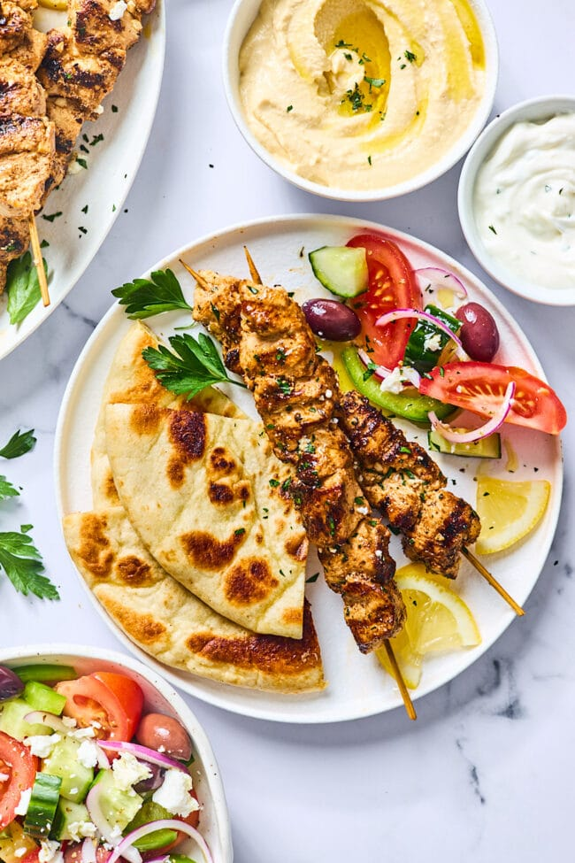 Greek chicken kabobs on plate with pita and Greek salad